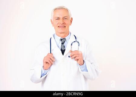 Portrait tourné d'un médecin mâle senior avec stéthoscope autour de son cou portant l'uniforme tout en se tenant sur un fond blanc isolé. Banque D'Images