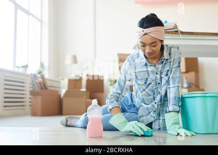 Portrait complet d'une heureuse femme asiatique nettoyer le sol dans une nouvelle maison ou un appartement après avoir bougez, copier l'espace