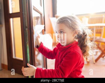 Une fille de trois ans aide au ménage. Elle nettoie les fenêtres avec une feuille de papier. Idée de passer le temps pendant la période de quarantaine du coronavirus covid-19.