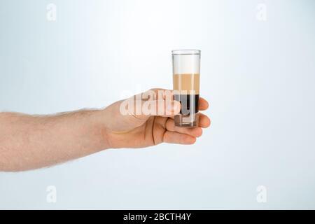 Gros plan d'une main tenant un verre de cocktail en forme de b52 sur fond blanc avec espace de copie.