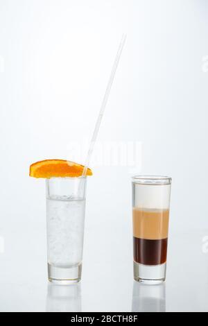 Gros plan sur un verre de cocktail b-52 sur fond blanc avec espace de copie.