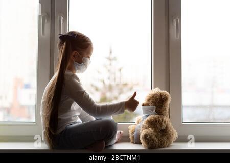 Un enfant triste et son ours en peluche sont tous deux dans des masques médicaux de protection. Enfants et maladie COVID-2019 concept de maladie