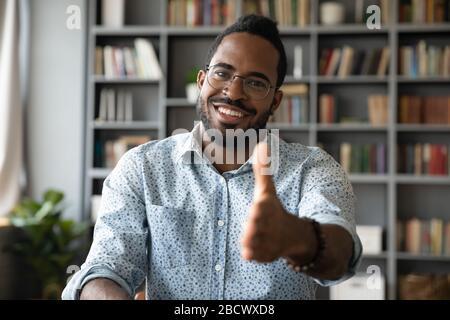 Portrait de l'homme souriant de biracial accueillir un nouvel employé sur le lieu de travail