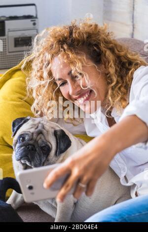 Les gens et les chiens restent à la maison concept avec joyeuse heureuse belle femme adulte prenant la photo de selfie avec son meilleur ami pug animal - les gens aiment tec Banque D'Images