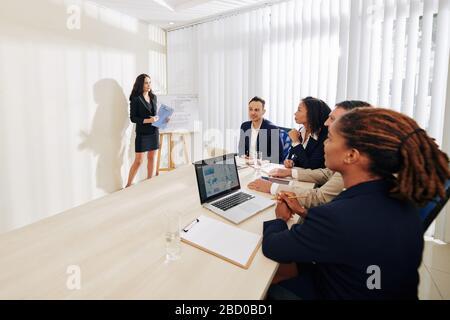 Groupe de personnes d'affaires positives à l'écoute d'une collègue de sexe féminin parlant de stratégie de développement et montrant des graphiques sur tableau blanc Banque D'Images
