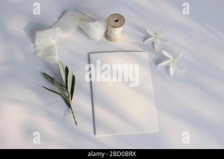 Mariage été papeterie scène maquette. Carte de vœux vierge, invitation, branche olive, carissa macrocarpa blanche, fleurs de prune natales et ruban de soie Banque D'Images