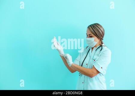 Femme médecin ou infirmière portant un masque, robe et stéthoscope mettant sur des gants chirurgicaux sur fond bleu avec espace de copie. Banque D'Images