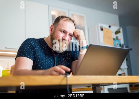 Un spécialiste INFORMATIQUE fournit des réunions en ligne non pas depuis son bureau mais depuis sa maison, son travail à distance, son travail à domicile. Temps de quarantaine