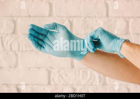 Gros plan de l'homme portant des gants médicaux en latex bleu sur les mains. Médecin professionnel mettant des gants de protection stériles pour l'examen du patient à l'hôpital. Banque D'Images