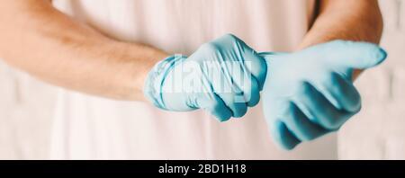 Bannière homme de fermeture portant des gants médicaux en latex bleu sur les mains. Médecin professionnel mettant des gants de protection stériles. Préparation pour examen patient Banque D'Images