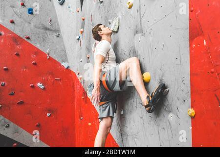 Grimpeur sportif se déplaçant sur une roche raide, grimpant sur un mur artificiel à l'intérieur. Sport extrême et concept de bouldering Banque D'Images