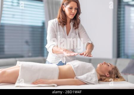 Soin réiki concentré faisant la séance de thérapie avec une jeune belle femme dans un centre de santé spa.