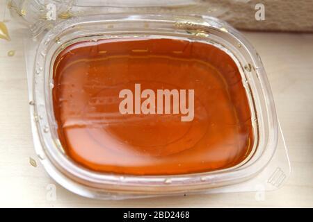 miel naturel à vendre dans des contenants en plastique . miel dans une boîte en plastique sur fond blanc . Banque D'Images