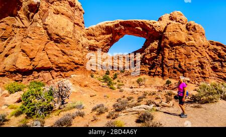 Femme sur un sentier de randonnée à l'Arc de fenêtre Sud dans la section Windows dans le désert du parc national d'Arches, Utah, États-Unis