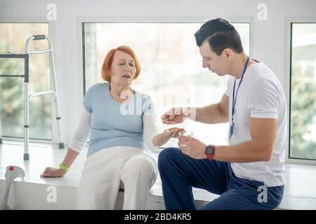 Une femme senior aux cheveux rouges gentille prend sa pilule Banque D'Images