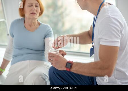 Jeune médecin professionnel donnant des pilules à son patient Banque D'Images