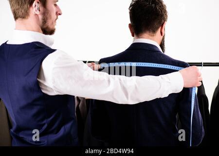 Mesure sur mesure du client en studio. Mesure du dos de la veste. Client de mesure sur mesure pour un vêtement sur mesure. Banque D'Images