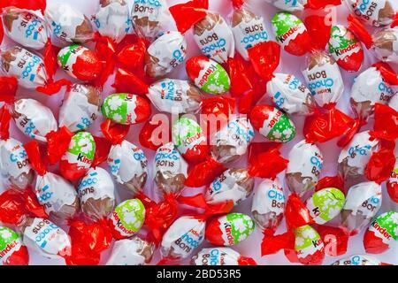 Lait Kinder et mini-œufs Choco-Bons et Kinder aux noisettes, chocolat au lait et noisettes laiteuses - chocolats étagés sur fond blanc Banque D'Images