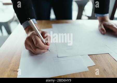 Fermez les mains en signant des documents dans un bureau moderne avec fenêtre en arrière-plan. Stylo à la main, papiers sur le bureau en bois, fond futuriste.