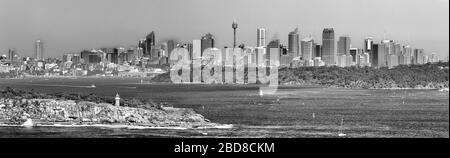 Vue contraste noir blanc de la ville de Sydney CBD sur les eaux du port de Sydney derrière la tête sud avec phare dans un large panorama de North Head.