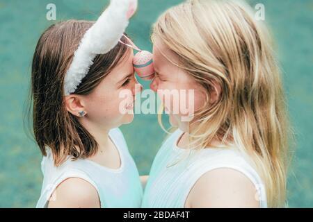Mignons petites soeurs portant des oreilles de lapin le jour de Pâques d jouer avec des œufs peints le tenant entre leurs front. Gros plan. Banque D'Images