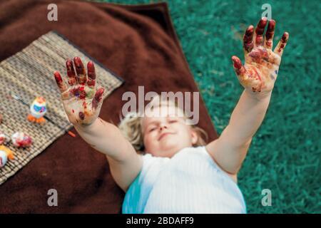 Mignonne petite fille layong sur la couverture sur l'herbe dans l'arrière-cour et montrer sa sale avec des mains peintes, peindre des œufs de Pâques.