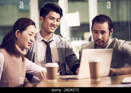 équipe de trois jeunes entrepreneurs asiatiques se réunissent au bureau avec une discussion utilisant un ordinateur portable au bureau Banque D'Images