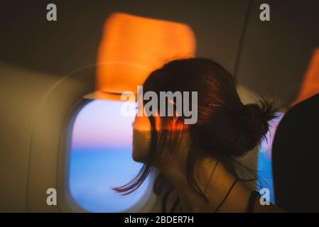 Portrait de la jeune femme en avion illuminé par la lumière du coucher du soleil