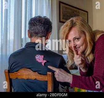 Blonde femme pris dans l'acte après avoir collé un poisson de papier pour le jour d'avril fools derrière un homme, apporte son index à sa bouche