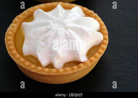 Tartelette avec crème au citron et écureuils fouettés. Gâteau rond sur une pâte à croûte courte. Tartelet à croûte courte et crème fouettée sur fond noir. Banque D'Images