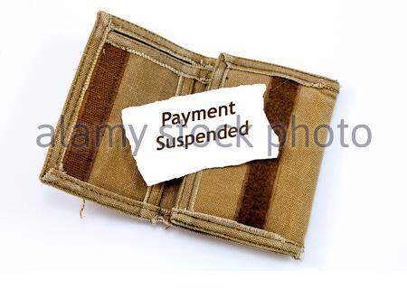 Portefeuille ancien et effiloché avec une note à l'intérieur indiquant « paiement suspendu » Banque D'Images