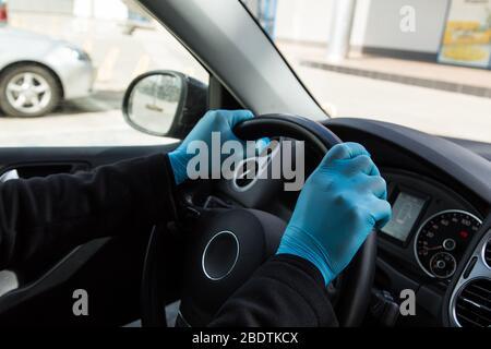 Homme gros plan en gants bleus assis à la roue d'une voiture pendant une épidémie Banque D'Images