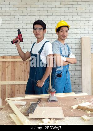 Deux menuiserie asiatiques pose avec confiance avant de commencer le travail de recevoir des commandes au lieu de travail du bois. Atmosphère de travail du matin dans l'atelier Banque D'Images