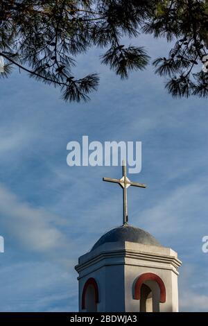 La croix blanche de l'église orthodoxe du village de Fanari, région de Xanthi, Grèce du Nord, clocher vue partielle contre le ciel bleu avec couvert, encadré par des branches de pins
