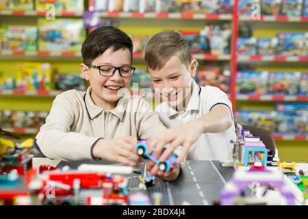 Les enfants jouent dans le concepteur à la table. Deux garçons jouent avec des blocs de plastique de couleur dans le centre de jeu, l'école