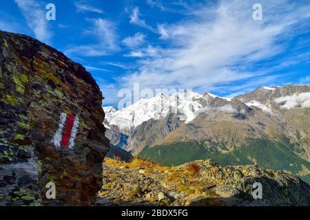 Panneau rouge et blanc sur la pierre dans les Alpes suisses. Banque D'Images
