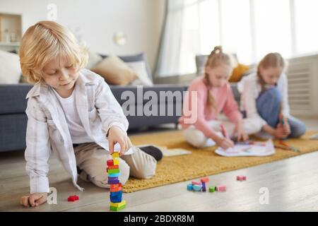 Petit garçon avec cheveux blond jouant sur le sol avec des jouets avec ses deux sœurs dessinant dans l'arrière-plan dans le salon Banque D'Images
