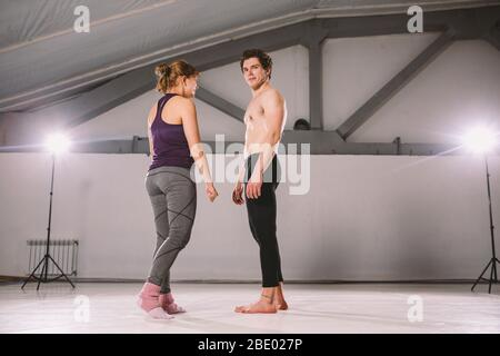 Le thème de l'acroyoga et du yoga pose. Acroyogis pratique. Avec le rétroéclairage studio. L'homme de base lance la femme Pops Flyer en vol vers le haut. Position Banque D'Images