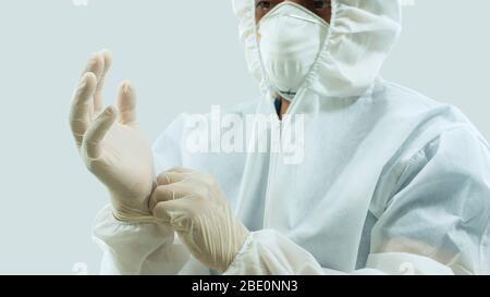 Médecin avec masque et costume blanc de bioprotection mettant des gants en latex sur les mains sur fond blanc Banque D'Images