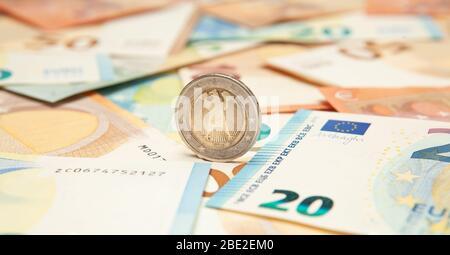 La monnaie en euros roule sur un fond de billets. Banque D'Images