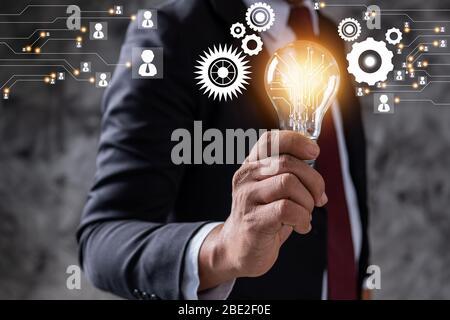 Innovation et idée d'un leader professionnel de l'entreprise qui tient une ampoule d'éclairage, gestion de la pensée et concept de puissance technologique Banque D'Images