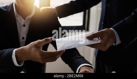 Gros plan sur la main du Manager donnant des bonus d'argent dans l'enveloppe papier à un employé de bureau heureux, félicitant l'employé avec l'augmentation du salaire ou de la promotion comme