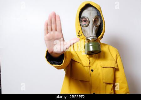 Un homme dans un masque à gaz pour résister au virus COVID-19, en levant les mains comme signal d'arrêt