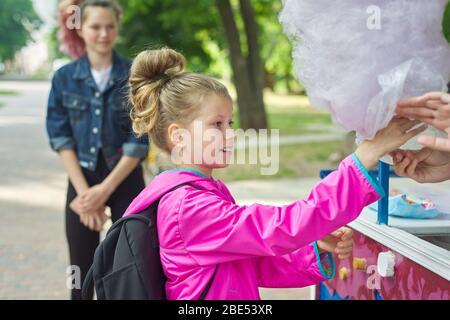 Enfants avec bonbons en coton. Fille enfant achetant rose sucre doux nuage. Banque D'Images