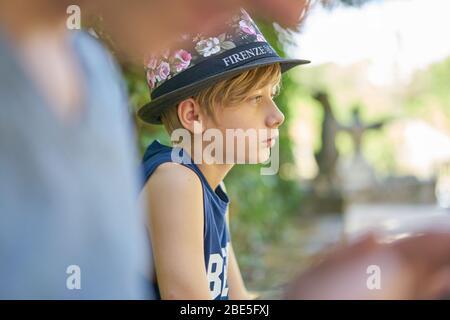Gros plan d'un garçon avec un chapeau debout dans la verdure et regardant triste à cause de problèmes Banque D'Images
