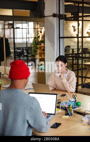 Image de jeunes collègues multiethniques, femmes et hommes, assis à la table et travaillant sur des ordinateurs portables au bureau Banque D'Images