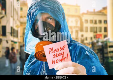 Un homme dans un masque à gaz contient une note avec le texte. Concept de rester à la maison en raison de la pandémie de covid-19 Banque D'Images