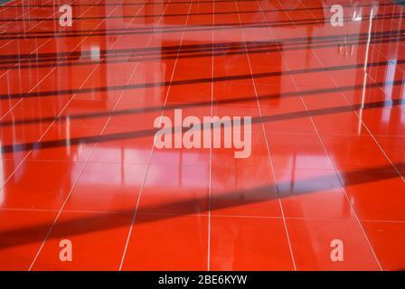 Structure abstraite du plancher rouge avec ombres et réflexions Banque D'Images