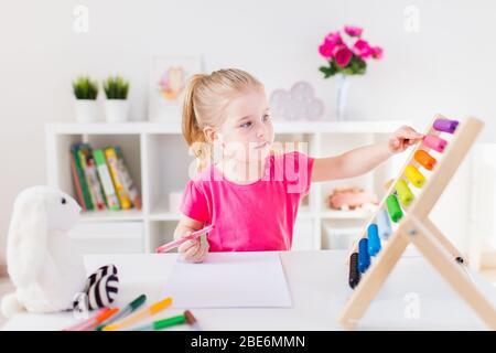 Petite fille blonde souriante assise au bureau blanc et comptant sur l'abacus coloré dans la salle de classe. Éducation à la maison.