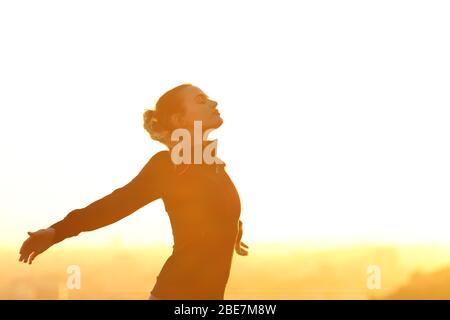 Profil d'un coureur qui respire profondément l'air frais qui dépasse les bras au coucher du soleil